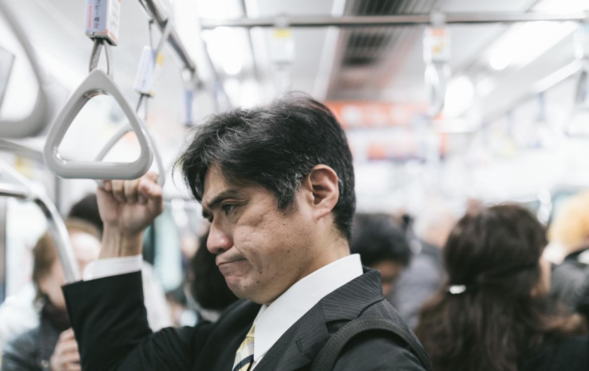 なんか臭いな。電車に乗っている顔をしかめる男性