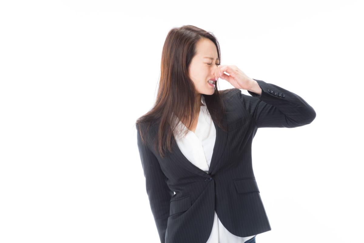 かおを背けて鼻をつまむ女性の画像