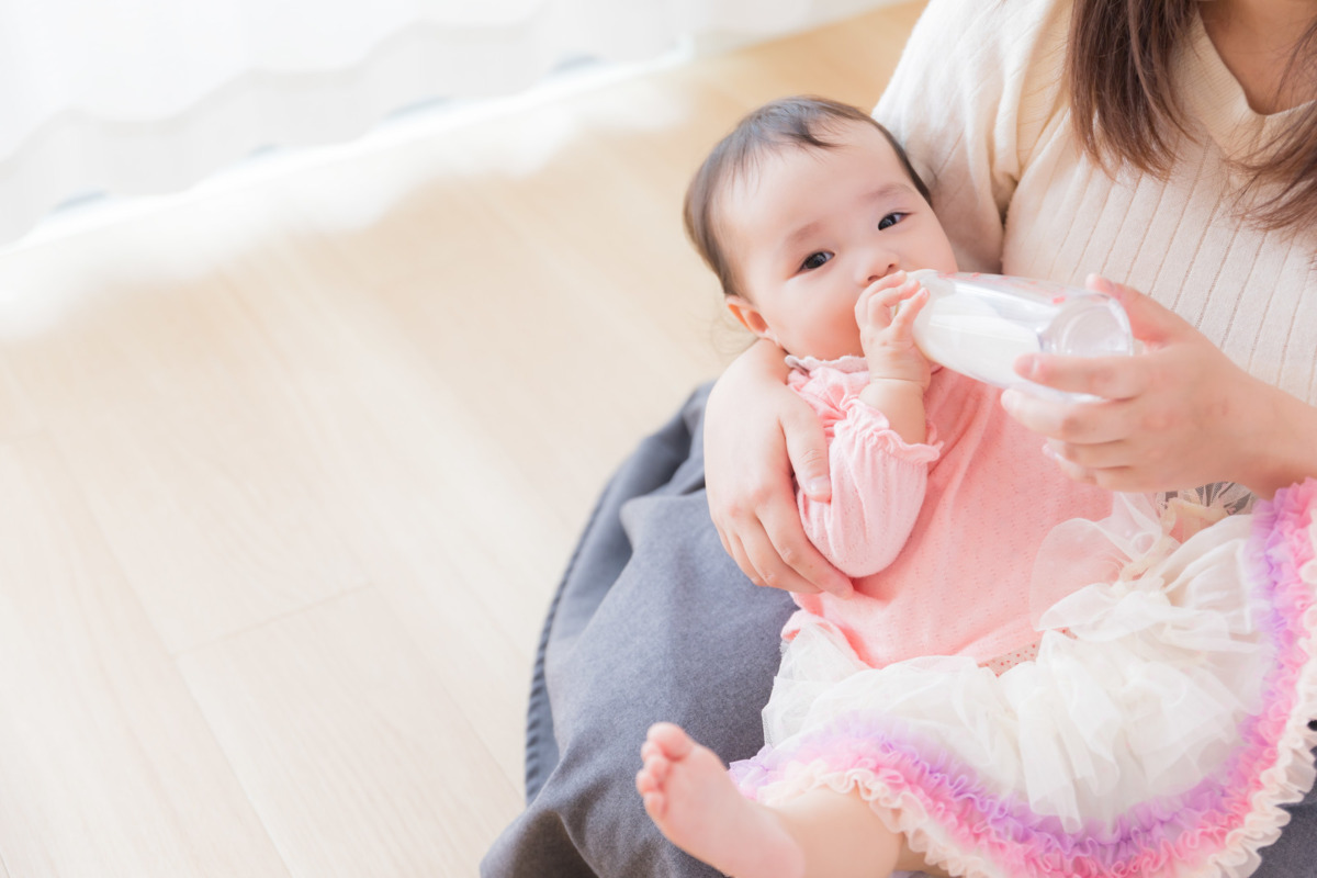 ママに抱っこされてミルクを飲んでいる赤ちゃんの画像