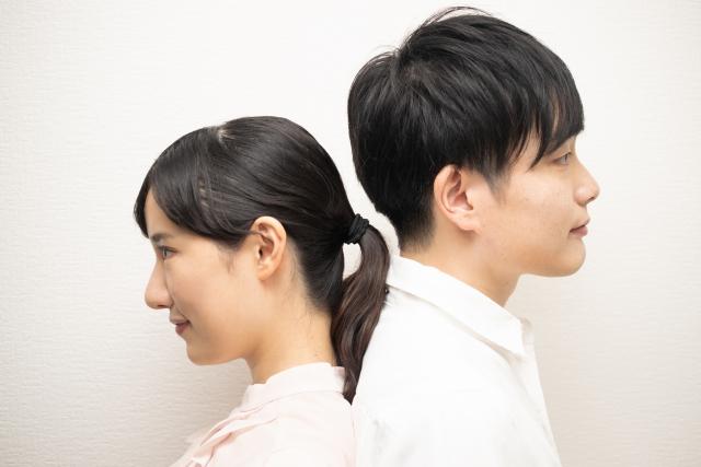 背中を引っ付けているカップル
