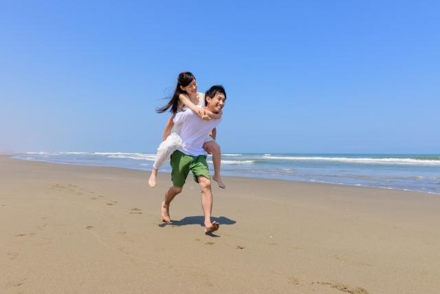彼女をオンブして砂浜を走っている彼氏