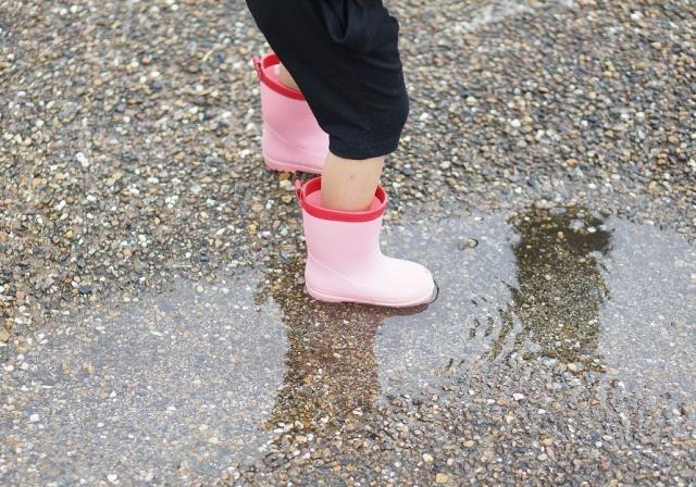 水溜まりと長靴をはいた子供の足元