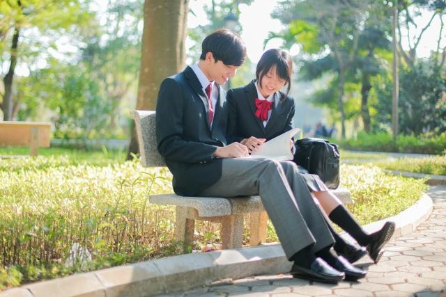 昼間の明るい公園で高校生の男女がおしゃべりしている