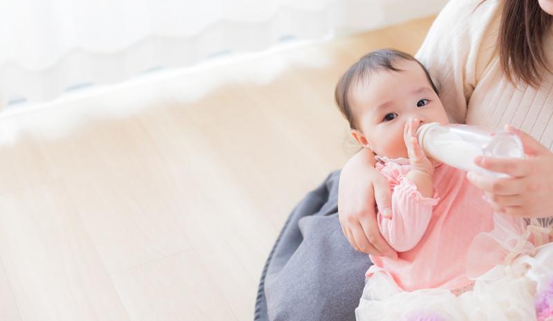母親に抱っこされてミルクを飲む赤ちゃん