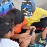 スマホでゲームに夢中で遊ぶ子供
